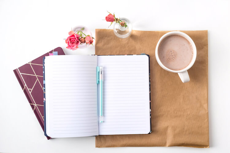 Image shows an open notebook laying across a desk. There's a closed notebook or journal lying beneath it, and a cup of tea to one side.