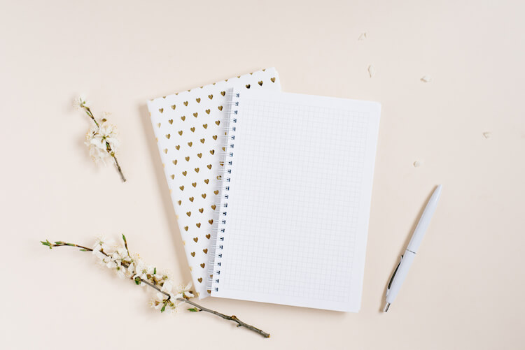 Self discovery journal prompts | Image shows a journal on top of a pad, with flowers and a pen laying beside them.