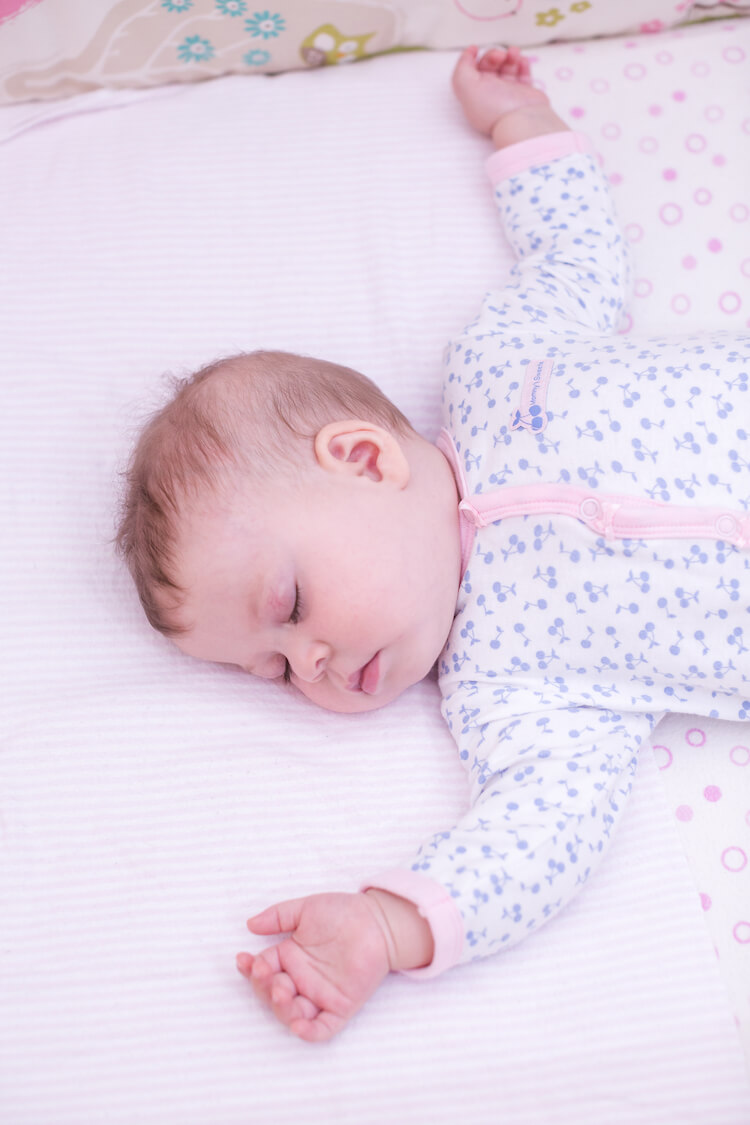 Sleep regression at 7 months.   Image shows a sleeping baby wearing a blue floral babygro.
