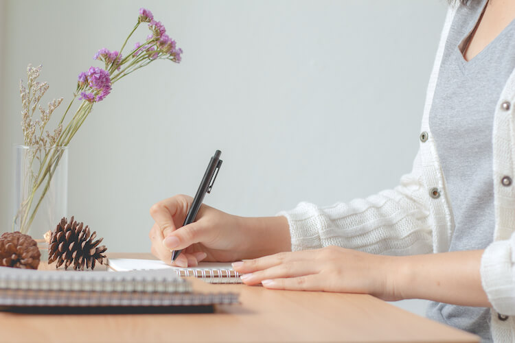 Image shows a woman writing at a desk. There's a spring of lavender in a vase in front of her.