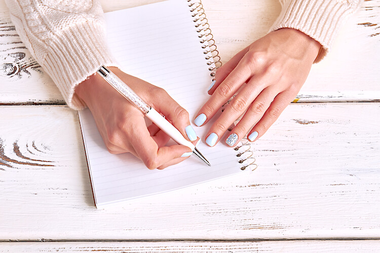 Image shows a woman writing in a notebook. She wears pale blue nail varnish and a creamy jumper.