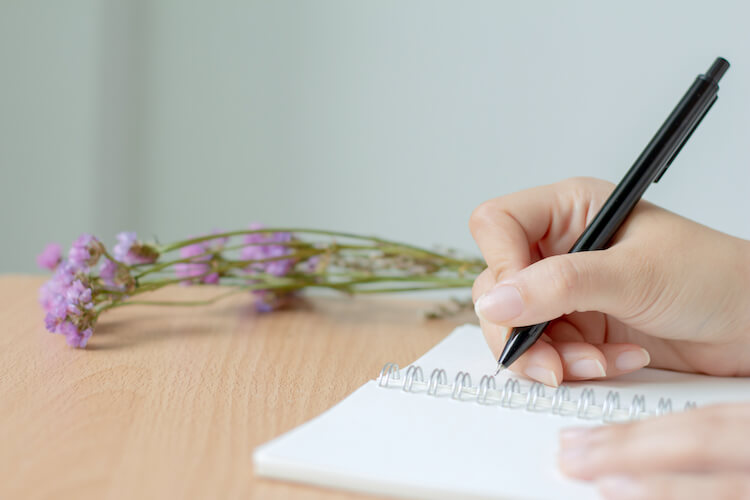 Image shows a woman writing in a notebook with a spring of flowers beside her.