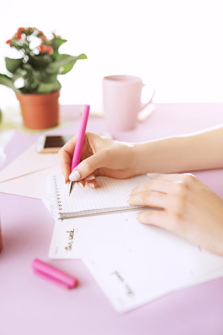 Image shows a woman writing in a journal. The desk is pink and there's a pot plant in the background.